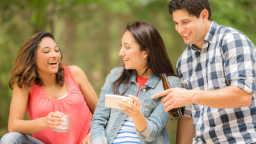 Two young women and one man view a social media post on their cell phone. The woman in center is holding the smart phone while the two friends  view the post, text message, tv show, or video.  Latin descent, caucasian, and mixed race group of people. Beautiful spring or summer nature background. Park, or backyard setting.